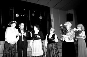 Režisori Intu Kalniņu (no kreisās) Skroderdienas Silmačos stilā sveic aktieris Juris Žūriņš un Limbažu senioru koris Atvasara