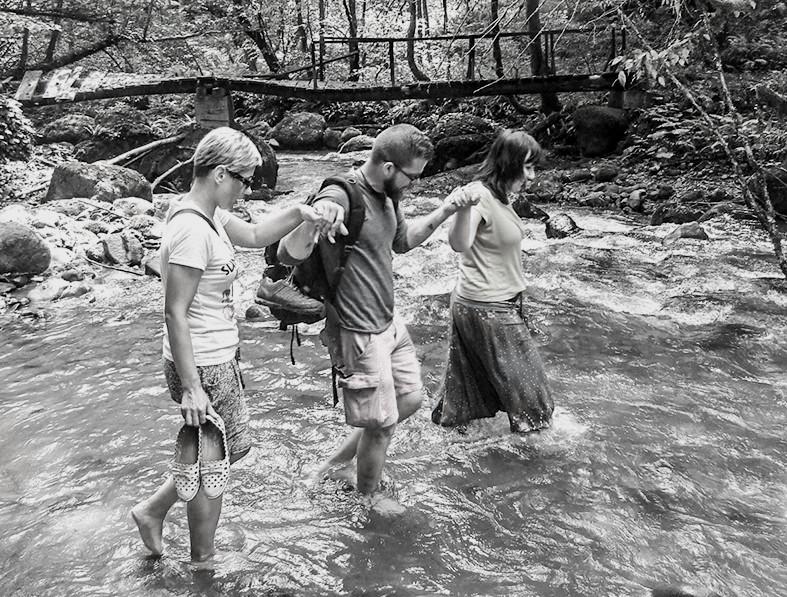 Jānis Roļskijs palīdz Džeinai Bērziņai (no kreisās) un Inesei Vaivarei pārvarēt kalnu upi